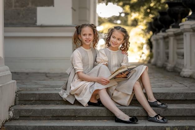 Две девочки из учениц начальной школы читают книгу во дворе академии.
