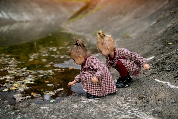 바위가 많은 해안에 있는 두 소녀가 막대기로 가을 웅덩이를 따고 있다