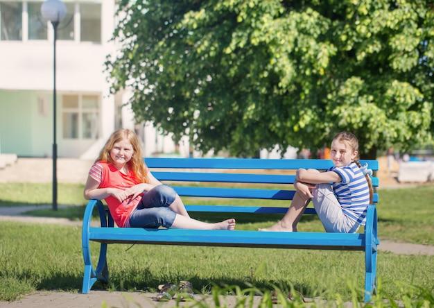 Две девушки на скамейке в парке