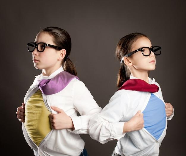 Two girls opening her shirt like a superhero