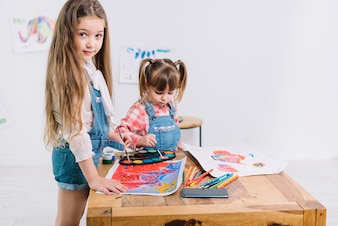Two girls painting with aquarelle on paper