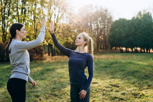 Two girls in the park are exercising and clapping their hands.