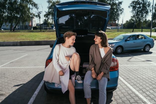 Due ragazze nel parcheggio del bagagliaio aperto
