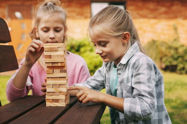 2人の女の子が家の近くで屋外で木のボードゲームをします