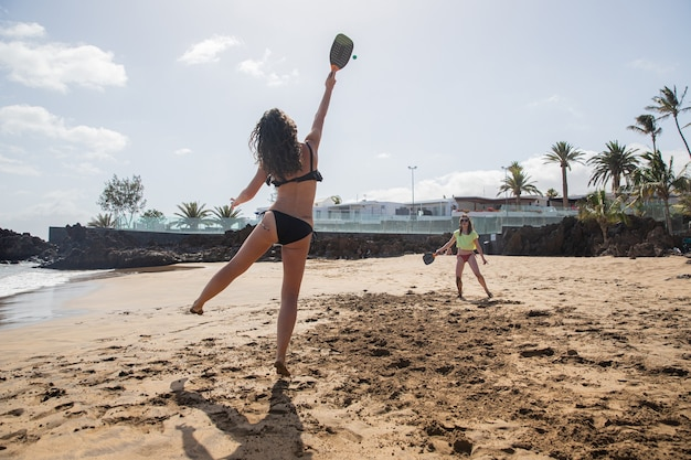 Two girls play beach tennis and have fun on their vacation.