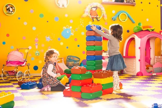두 여자는 놀이방에서 큰 벽돌을 가지고 노는
