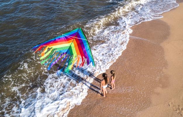 Two girls play with a kite by the sea