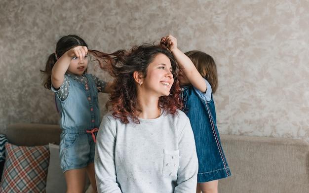 二人の女の子が母親と遊んだり、髪をしたり、髪をとかしたりします。幸せで陽気なお母さん