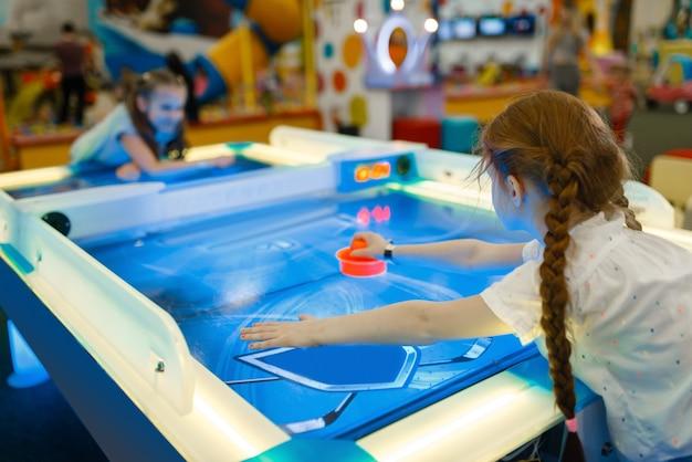 Две девушки играют в воздушный хоккей в развлекательном центре. детские праздники, детское счастье, счастливые дети на детской площадке