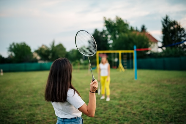 Two girls playing badminton on a green field.