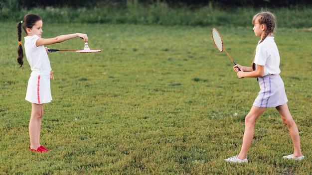 공원에서 배드민턴을 재생하는 두 여자