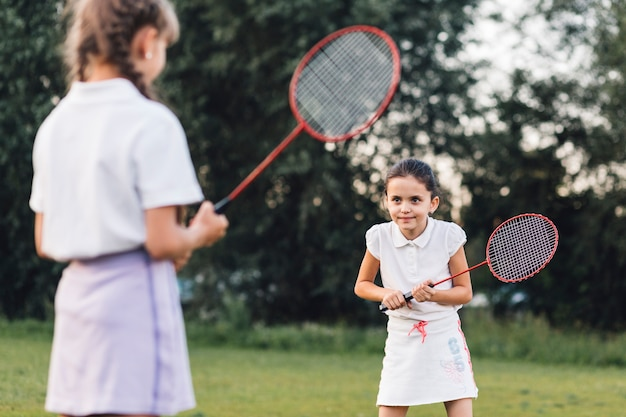 Two girls playing badminton in the park