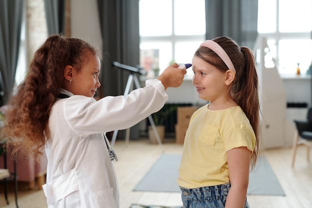 彼らが家で遊んでいる小さな患者を調べる白いコートを着た病院の女の子で遊んでいる2人の女の子