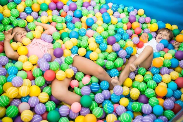 Две девушки играют в бассейне с красочными пластиковыми шарами в игровой комнате