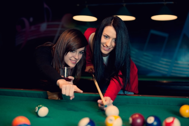 Two girls playing pool game