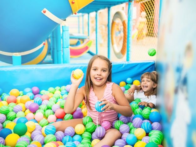 Two girls playing in pool with colorful plastic balls in game room.