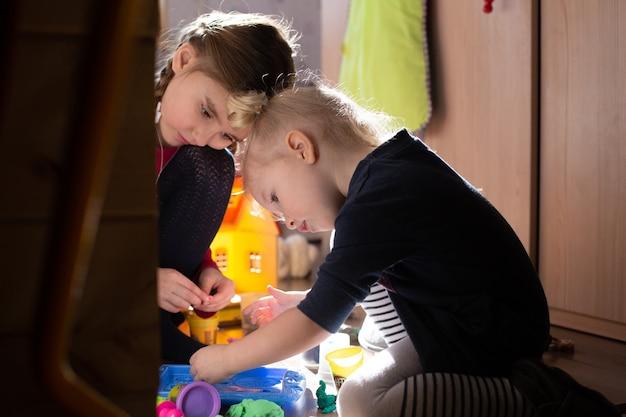 床に座って朝の太陽の光の中で一緒に遊んでいる2人の女の子。のんきな子供時代のコンセプト。屋内