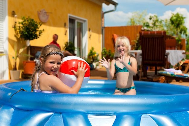 Two girls playing with ball in the backyard pool