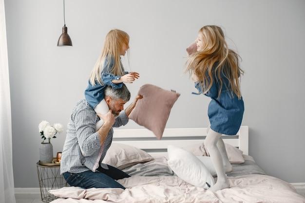 Две девушки играют с подушками в спальне. вечеринка в спальне.