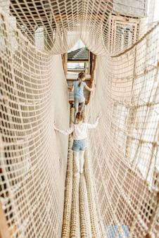 Две девочки играют в веревочной сети, детский игровой центр