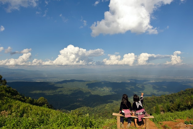 Two girls point on cloudy sky at the top of chiangmai city thailand