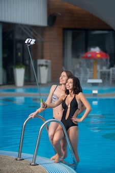 Two girls posing against the swimming pool and making selfie photo with selfie stick