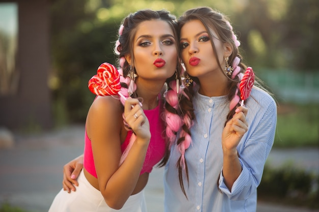 Two girls posing and making duckface with candies heart on stick.