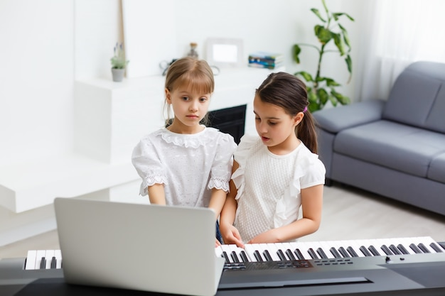 Two girls practice sheet music on one musical instrument