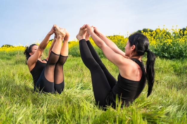 Две девушки практикуют позы йоги на природе