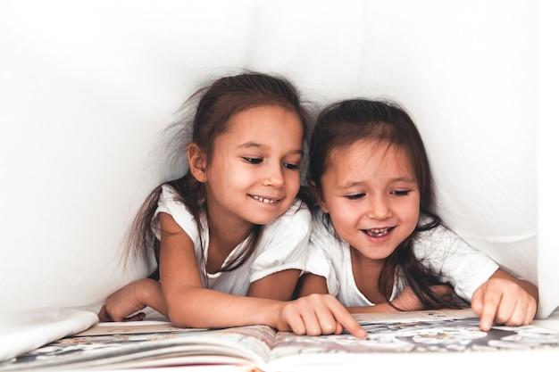 Две девушки читают под одеялом