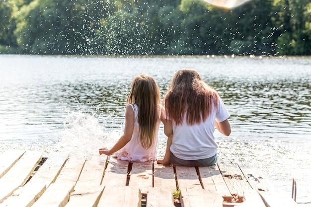 두 여자는 햇빛의 광선에 강가에서 휴식을 취합니다. 하이라이트가있는 사진