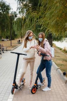 Две девушки катаются на скутерах и фотографируются