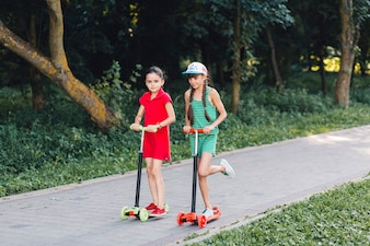 Two girls riding on push scooter in the park