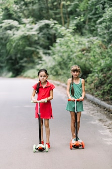 Two girls riding scooters on road