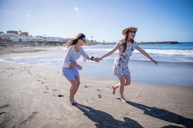 두 소녀는 손을 잡고 해변에서 달리고, 휴가를 보내는 동안 웃고 농담을합니다. 소녀 파워 개념.