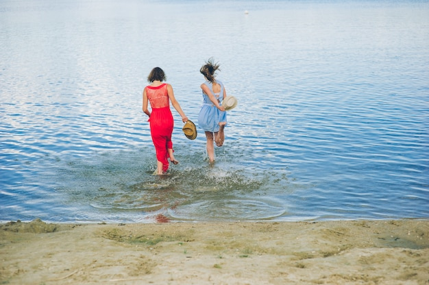Two girls run into water