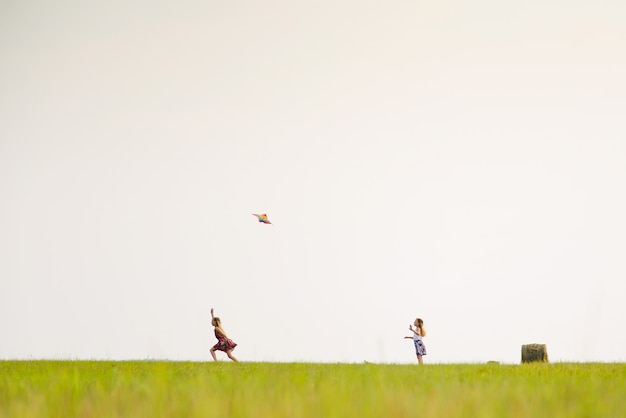 Two girls run on a summer field with a kite