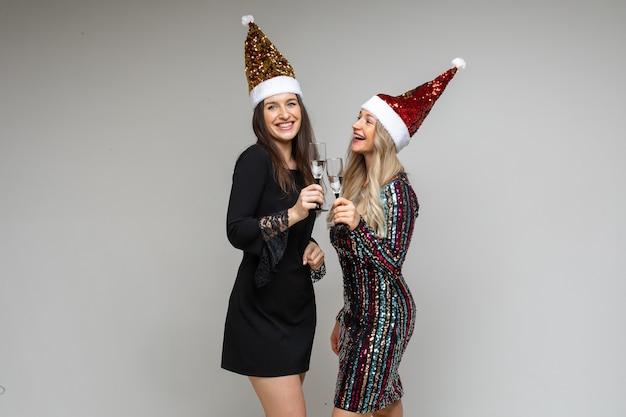 Due ragazze in cappelli di babbo natale con bevande alcoliche.