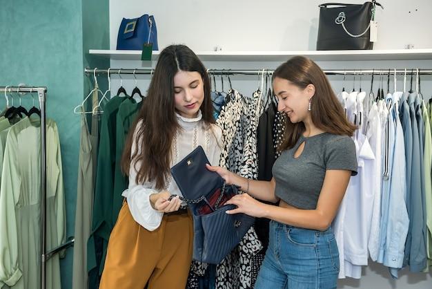 Две девушки делают покупки в магазине. подружки выбирают в торговом центре лучшую современную одежду. стиль жизни