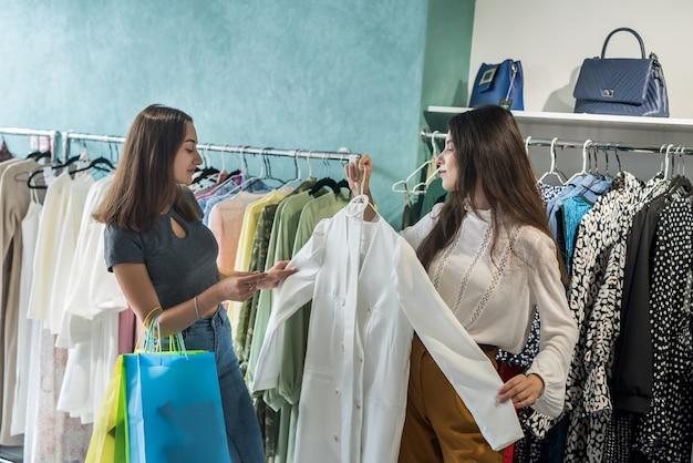 가게에서 쇼핑하는 두 여자. 여자 친구는 쇼핑몰에서 최고의 현대 옷을 선택
