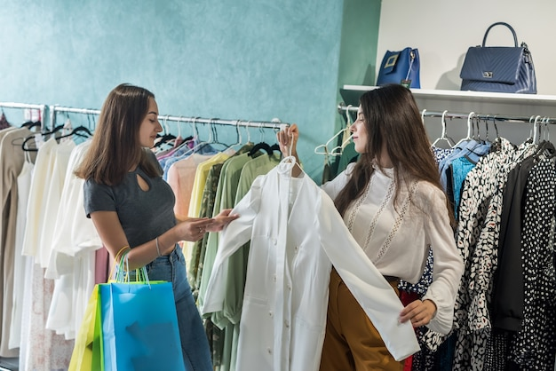 Two girls shopping in the store. girlfriends choose the best modern clothes in mall