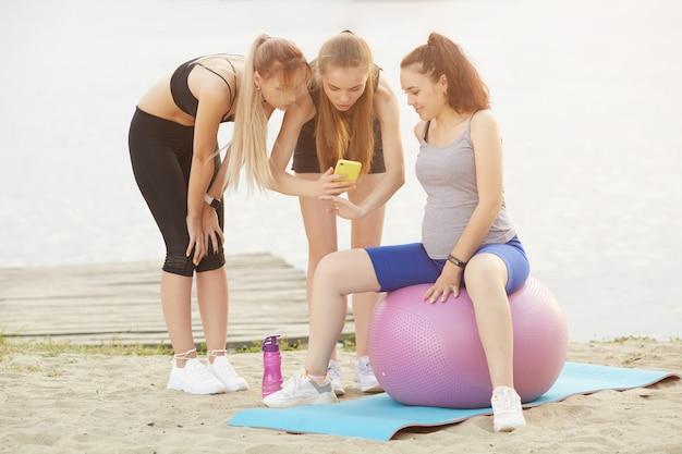 Две девушки показывают своей беременной подруге, как правильно выполнять упражнения на гимнастическом мяче
