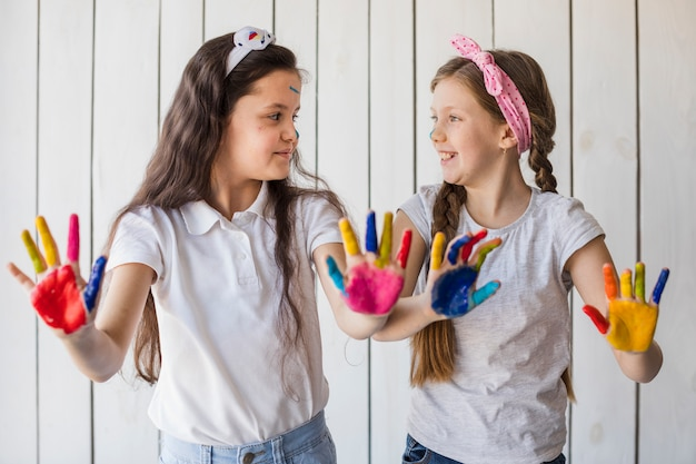 Two girls showing colorful painted hand looking at each other