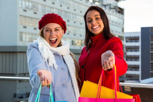 2人の女の子が外に買い物袋を見せて