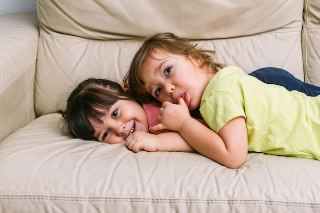 Two girls sister embraced, lying on a sofa playing