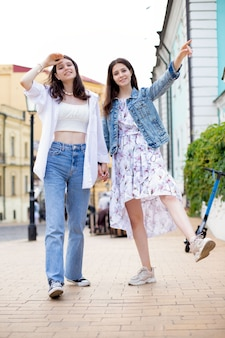Two girls sisters in casual clothes together fun walking down the street in summer