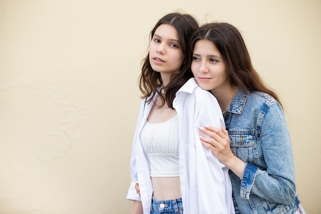 Two girls sisters in casual clothes on a yellow isolated background