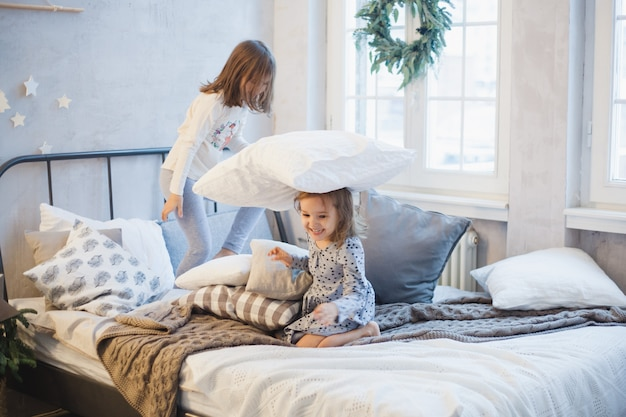 Two girls, sisters fighting pillows on the bed, the window decorated with a christmas wreath, life, childhood
