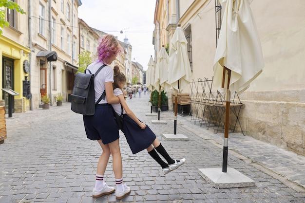 학교에가는 길에 재미 두 여자 자매. 십 대 소녀는 더 젊고, 아이들은 웃고, 화창한 여름날 도시에서