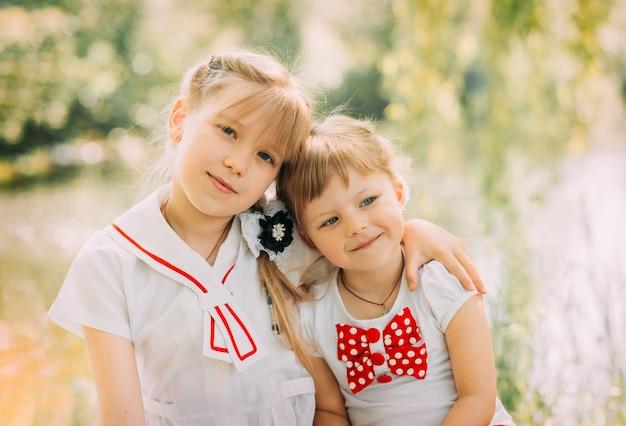 自然の中で夏に抱き合って楽しんでいる2人の女の子の姉妹。幸せな子供時代と夏のレジャーの概念。子供たちは屋外で遊ぶ。
